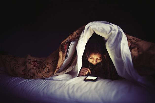 Criança com smartphone debaixo da coberta