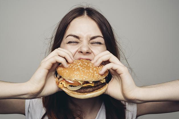 Jovem comendo lanche de fast-food