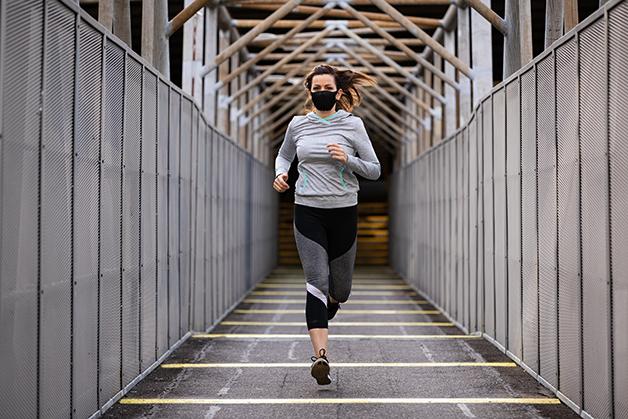 Mulher correndo de máscara durante a pandemia