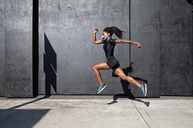 Mulher correndo de máscara durante a quarentena