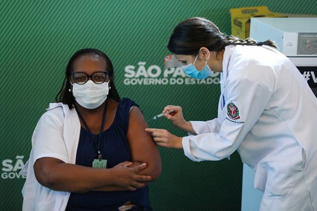 Mônica Calazans recebendo a primeira dose da vacina em solo brasileiro