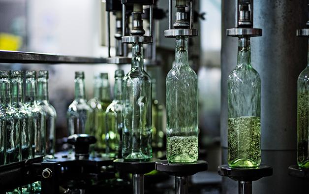 Vinho sendo inserido em garrafa durante sua fabricação