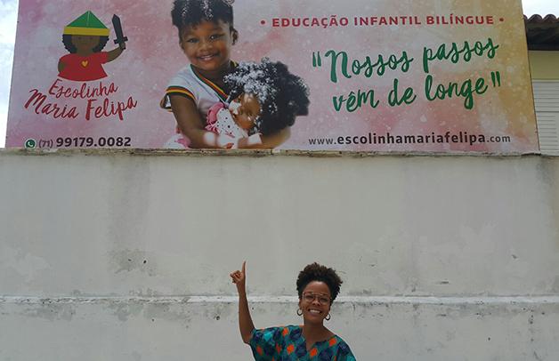 Bárbara Carine diante da placa da escolinha Maria Felipa em Salvador
