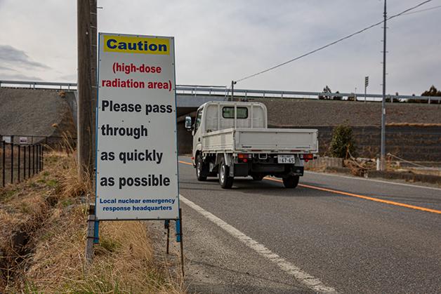 """""""Cuidado: área de alta radiação. Por favor, passe o mais rápido possível"""", diz a placa na entrada de Namie, na Zona de Exclusão"""