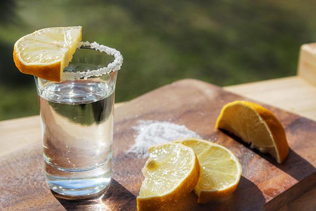Um copo de tequila com rodelas de limão e sal