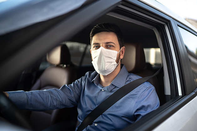 Motorista de Uber dirigindo com máscara