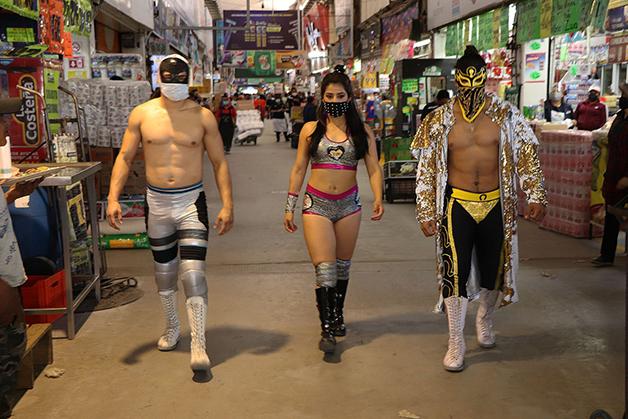 Astros da Lucha Libre mexicana distribuindo máscaras no Mercado Central da Cidade do México
