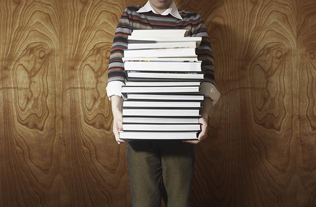 Homem carregando pilha de livros