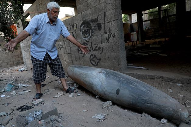 Homem palestino diante de uma bomba israelense que falhou em explodir em maio de 2021