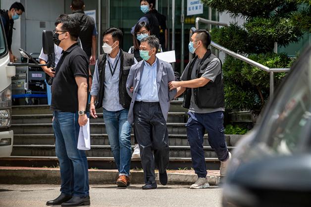 O diretor Chow Tat Keun sendo preso durante a operação contra o jornal
