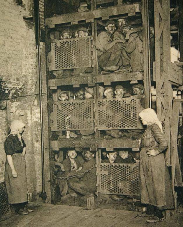 Mineiros saindo de uma mina de carvão após um dia de trabalho em um elevador na Bélgica em 1920