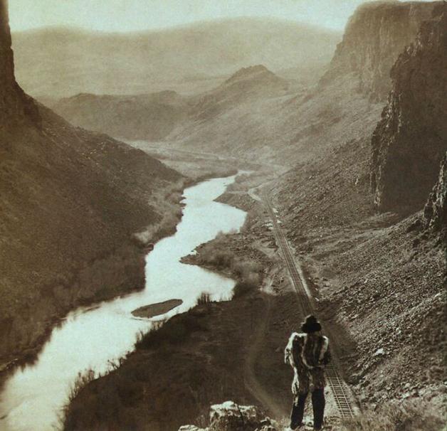 Um homem indígena em Nevada, nos EUA, olhando uma recém construída ferrovia em 1869