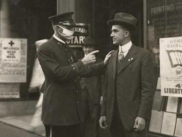 Policial repreende um homem em San Francisco, nos EUA, por não usar máscara durante a pandemia da Gripe de 1918