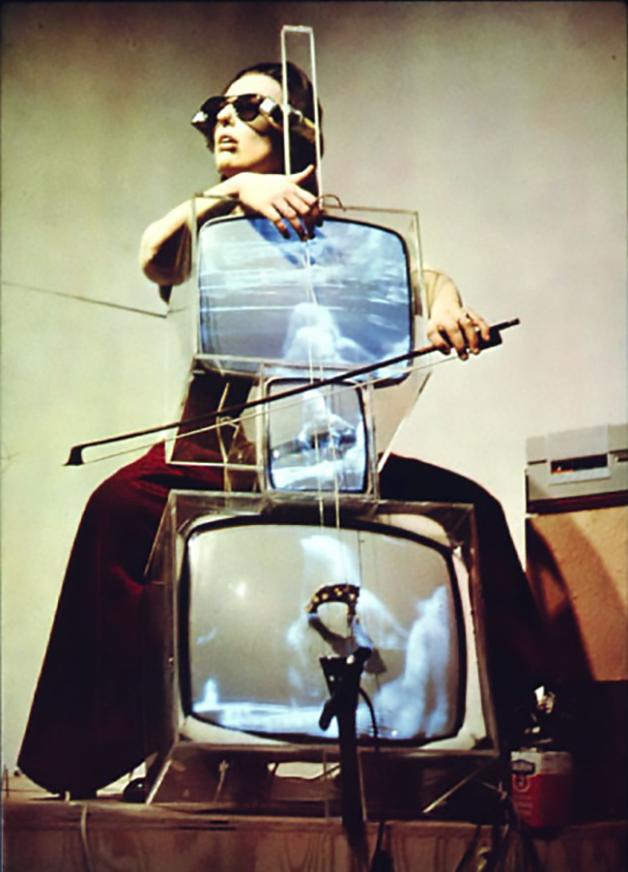 """Charlotte Moorman executando a peça """"Concerto para TV e Cello e Videotapes"""", de Nam June Paik, em 1971"""