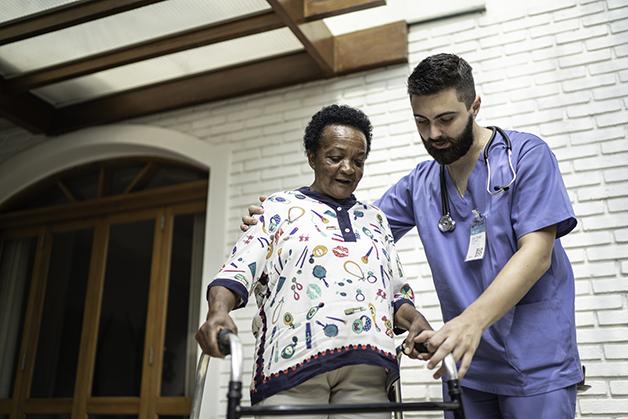 Un'infermiera aiuta a camminare un malato di Parkinson