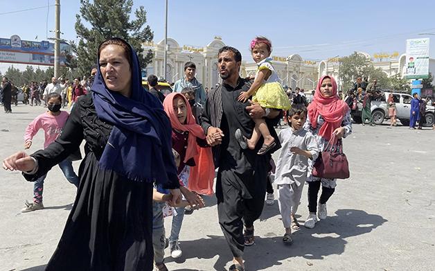 Família afegã nos arredores do aeroporto de Cabul, tentando fugir do país