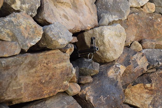 Cano de um AK-47 saindo das paredes de uma mina no Afeganistão
