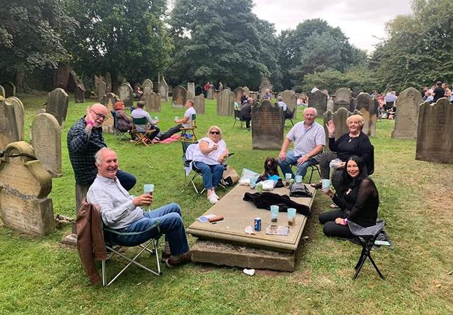 Festival da cerveja em igreja provoca indignação após visitantes posarem com bebidas em lápides