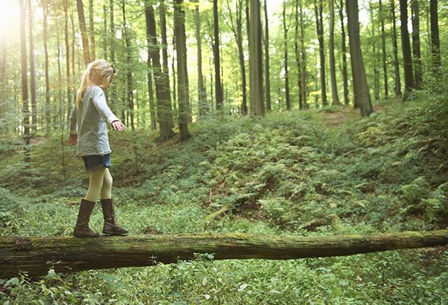 Criança caminhando sobre tronco de árvore
